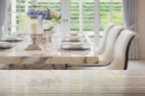 granite table top and blur of dining table and comfortable chairs in vintage style with elegant table setting